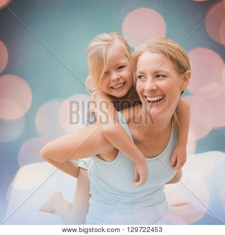 Cute little girl and mother on bed against background of multiple color