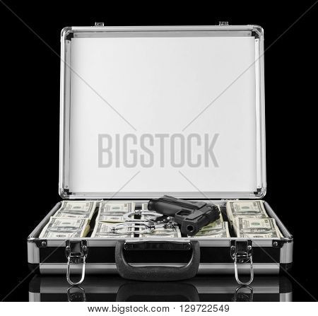 Dollars and a gun in a case isolated on a black background