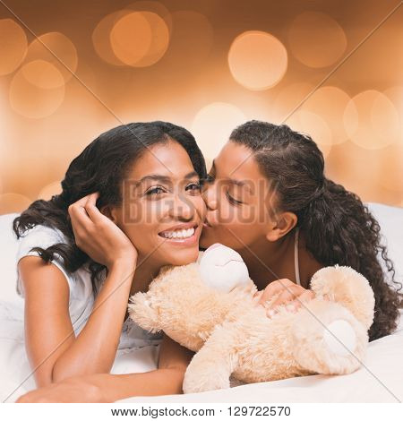 Pretty woman lying on bed with her daughter kissing cheek against glowing background