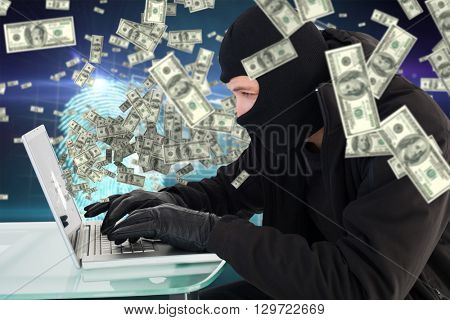 Robber sitting at desk hacking a laptop against digital security finger print scan
