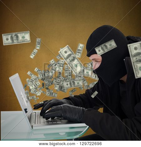 Robber sitting at desk hacking a laptop against orange background