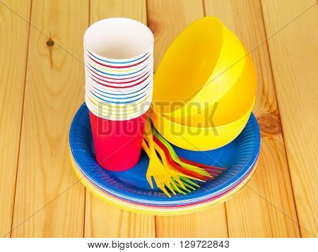 Colorful bright disposable tableware on a wooden table