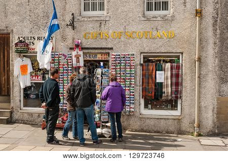 EDINBURGH SCOTLAND - MAY 15 2012: Tourists outside a gift shop in the Royal Mile in Edinburgh.