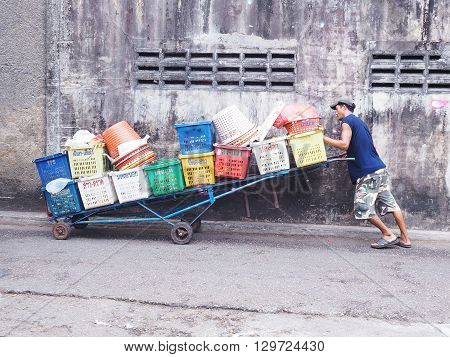 PHUKET THAILAND - MAY 04 2016: An unidentified man pushes barrow with many fruit baskets at the old town market on May 04 2016 in Phuket province Thailand.