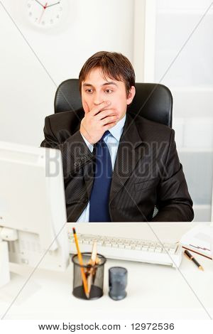 Shocked businessman sitting at office desk and looking at computer monitor