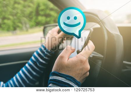 Female driving car and receiving smiley emoticon message on smartphone using mobile phone in traffic selective focus