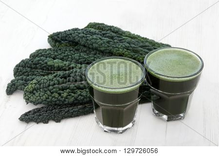 Kale health drink with fresh vegetable leaves over distressed white wood background. High in vitamins and antioxidants. Selective focus.