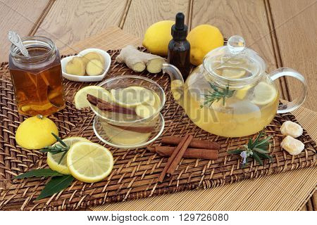 Honey, lemon, ginger and cinnamon drink for cold and flu relief with glass tea cup and pot, herbs, spices, medicine bottle, cough sweets and fresh fruit on wicker and bamboo mats over oak background.