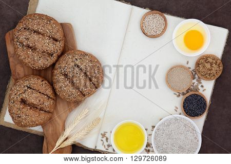 Seeded brown rolls with flour, yeast, egg, sugar, oil, poppy and sesame seeds, loose grain and wheat sheaths on hemp notebook over lokta paper background.