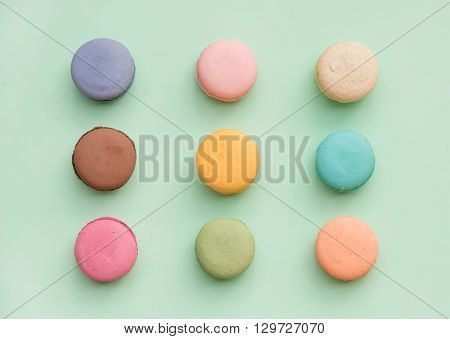 Sweet colorful French macaroon biscuits on pastel mint background, top view