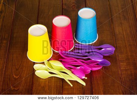 Colorful disposable cups and colorful spoons on dark wooden background