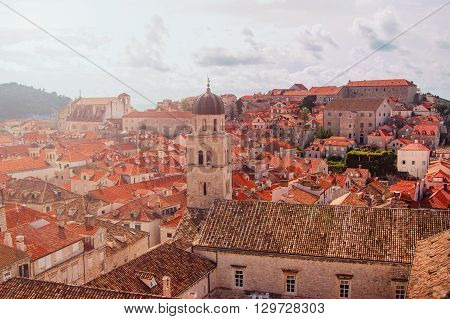 Sunrise over the old city of Dubrovnik, Croatia, Franciscan church with tower bell and roofs of old houses, warm filter applied