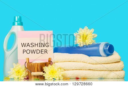 Clean towels with means for washing and yellow flowers on a blue background