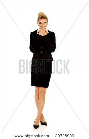 Young businesswoman covering with hand her mouth. Speak no evil concept