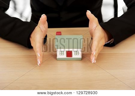 Businesswoman with small house behind the desk
