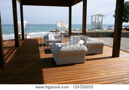 HERAKLION, CRETE, GREECE - MAY 13, 2014: The modern terrace with arm-chairs on the beach of Mediterranean coast of Crete, May 13, 2014, Greece.