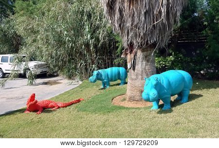 HERAKLION CRETE GREECE - MAY 13 2014: The two blue decorative hippopotamus and red crocodile on the terrain of luxury class hotel on the Mediterranean coast of Crete, May 13, 2014, Greece.