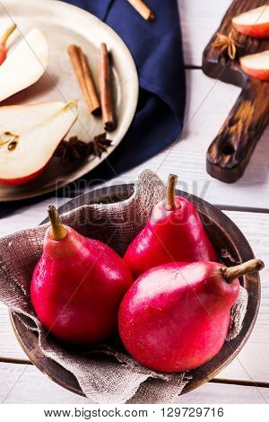 Red pears in ceramic bowl on white wooden background. Selective focus.