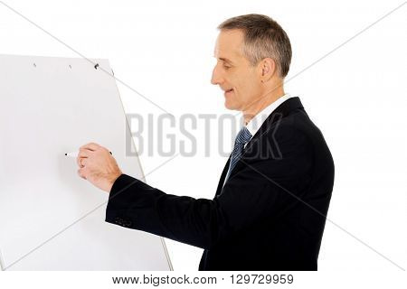 Male executive writing on a flipchart