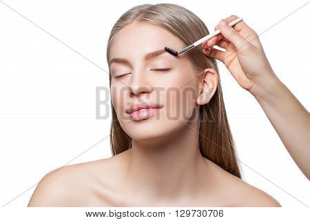 Beautician correcting eyebrows form on beautiful woman face. Beauty shot. Close-up. Isolated. Copy space.