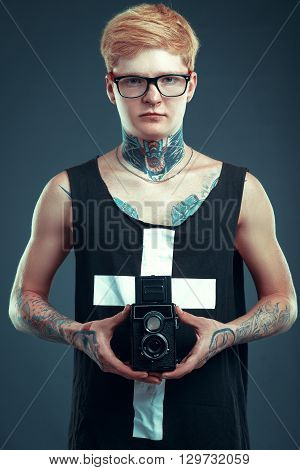 A Young Blond Man In Glasses With A Pierced Nose And A Tattoo Holding A Camera