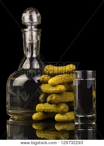 Decanter and glass with vodka and pickled cucumbers isolated on a black background