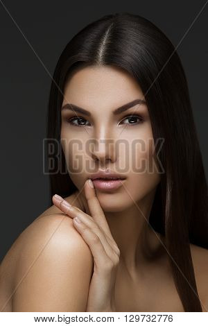 Beautiful young woman with perfect skin and straight shiny hair over dark background. Beauty shot, Copy space.