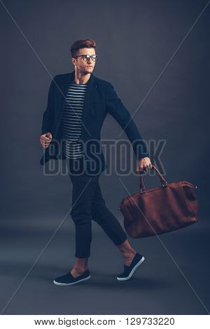 Style in action. Full length of confident young handsome man in glasses carrying bag and looking away while walking against grey background