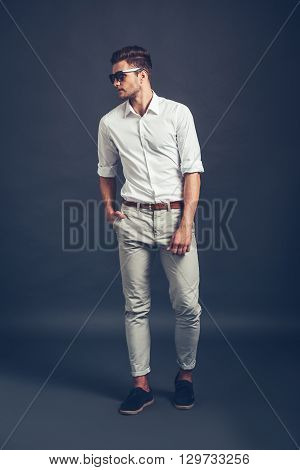 Casual and handsome. Full length of confident young handsome man keeping hand in pocket and looking away while standing against grey background