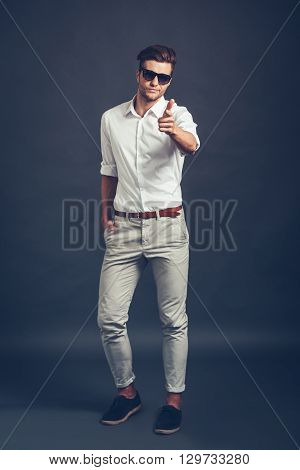 Maybe you? Full length of confident young handsome man  pointing you and looking at camera while standing against grey background
