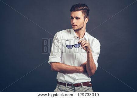 Loving his style. Confident young handsome man looking away while standing against grey background
