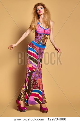 Fashion beauty sexy model in stylish bright clothes. Blonde woman in colorful luxury summer dress, glamor shoes with volume hairstyle, make up. Expressive playful vivid girl. Unusual creative lady.