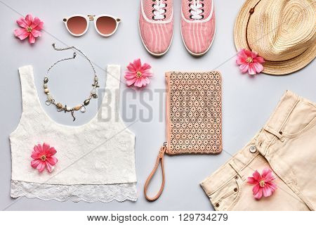 Street style. Summer Fashion girl clothes set, accessories. Trendy sunglasses, gumshoes, lace top, handbag clutch, necklace hat and flowers. Romantic lady. Creative urban overhead, top view on gray