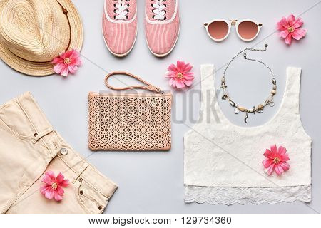 Summer, street style. Summer Fashion girl clothes set, accessories. Trendy sunglasses, gumshoes, top, fashion handbagclutch,hat,flowers. Summer lady. Creative urban summer overhead. Top view