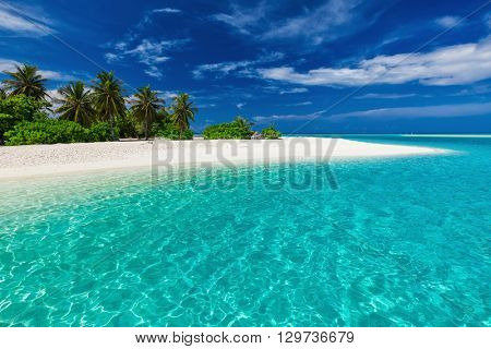 White sandy tropical beach with palm trees and blue lagoon on sunny day