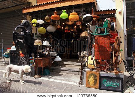 TEL AVIV-YAFO ISRAEL - APRIL 5 2016: Old vintage lamps toys furniture and other staff at entry to antiquities shop at Jaffa flea market in Tel Aviv-Jaffa Israel. Jaffa flea market is popular attractions for tourists and locals.