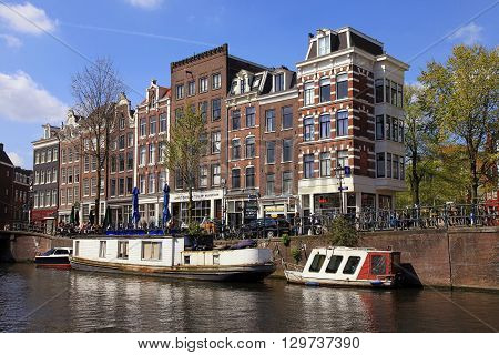 AMSTERDAM, NETHERLANDS - MAY 4, 2016: View of traditional houses and boats in Jordaan neighborhood and canals of Amsterdam, Netherlands. Amsterdam is the capital and most populous city of the Netherlands