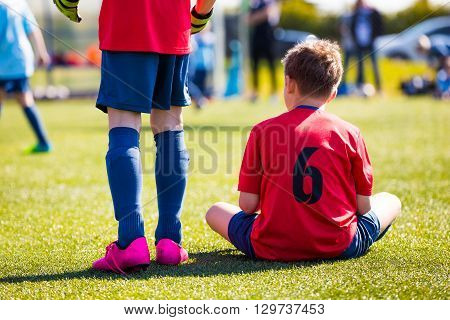 Youth Soccer Player sitting on sports venue. Youth sport team supporting teammates at the game.