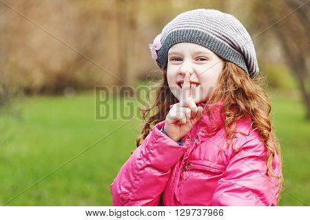 Little girl putting finger up to lips and ask silence in spring park.