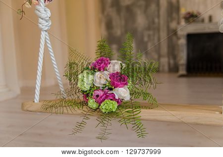 Purple and green flower bouqet lying on wooden swing