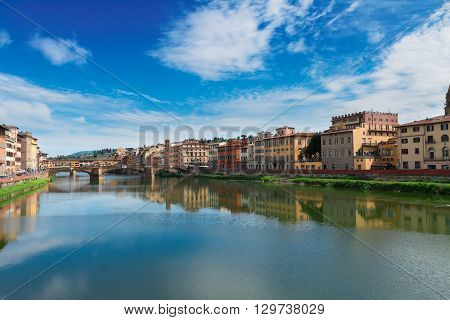 famous bridge Ponte Vecchio reflecting in river Arno at summer day, Florence, Italy