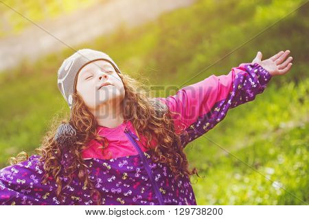 Little girl closed her eyes and breathes the fresh air in the park.