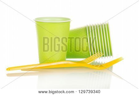 Green plastic cups and yellow fork isolated on white background