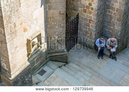 Mont St. Michel France - May 22 2012: Normandy tourists in a moment of rest in the ascent to the abbey.