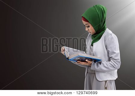 Image of asian muslim woman reading koran