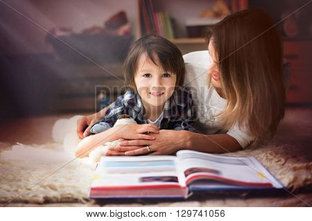 Young Mother, Read A Book To Her Child, Boy In The Living Room Of Their Home