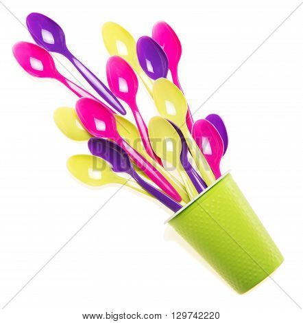 Multi-colored plastic spoons in the single cup isolated on white background