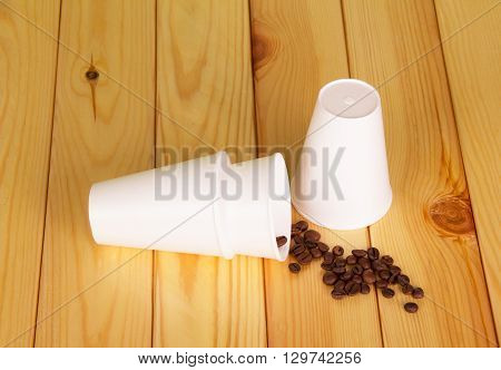 White disposable cups and coffee beans on a background of light wood