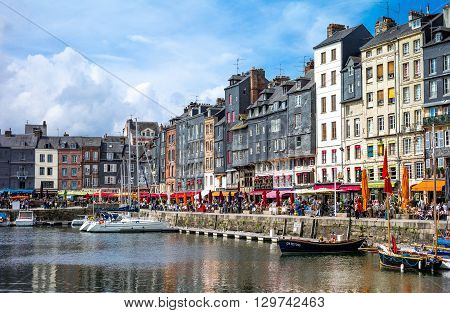 Honfleur France - May 19 2012: Normandy traditional houses and boats in the old harbor basin.