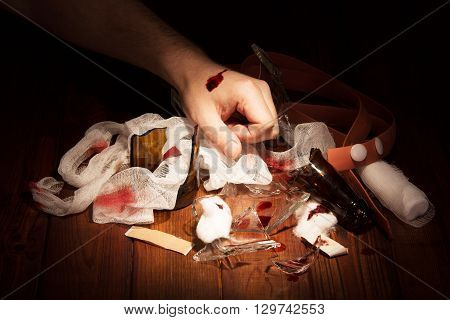 Man's hand chopped glass and the means to stop the bleeding in a dark wood